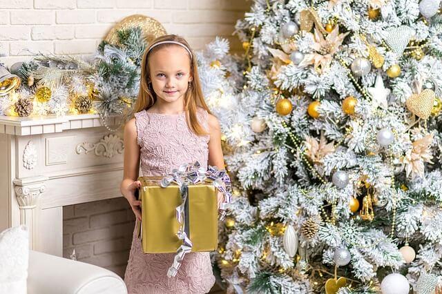 Geschmückter Weihnachtsbaum weiß mit Mädchen und Geschencken
