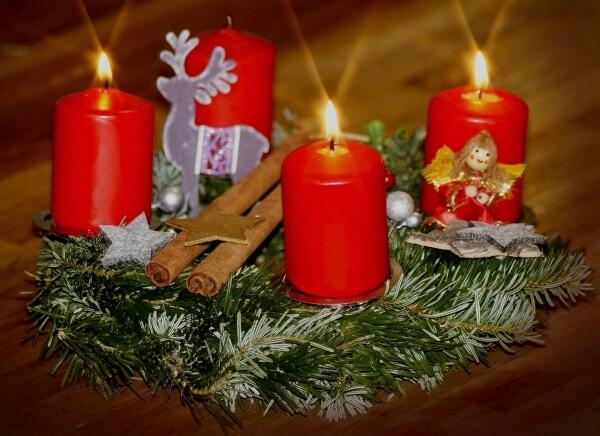 Echter Adventskranz Rot mit brennender Kerze.