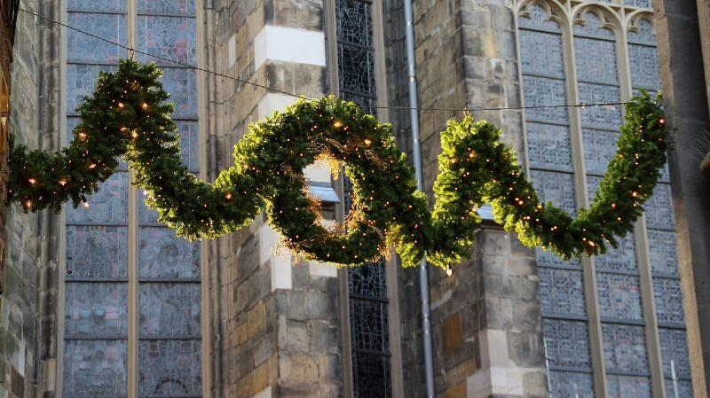 Weihnachtsgirlande mit Beleuchtung vor einer Kirche